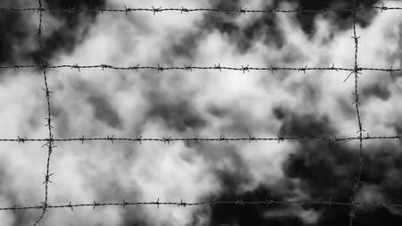 Imprisoned concept. Barbed wire strands with azure sky and white clouds as background Фото со стока
