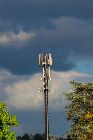 Electromagnetic radiation and environment issue. Telecommunication tower with 5G and 4G antennas among trees Фото со стока