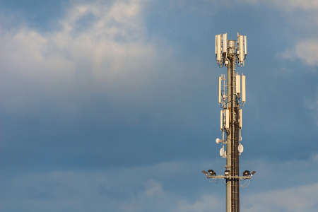 Electromagnetic radiation. Telecommunication tower with 5G and 4G antennas among clouds (with copy space)