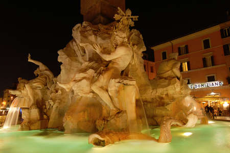 Night view of the famous Piazza Navona square in Rome with the wonderful Fountain of Four Rivers Редакционное