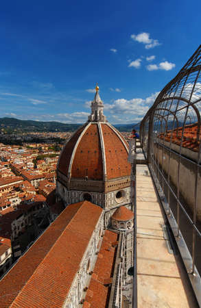 Tourists watching the famous Santa Maria del Fiore (St Mary of the Flower) renaissance dome and city historic center from cathedral bell tower panoramic terrace Редакционное