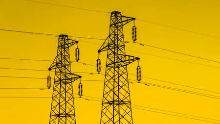 Electric power industry. Transmission towers or electricity pylons with golden sky Фото со стока