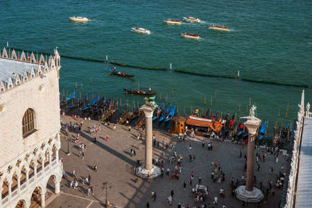 Tourism in Venice. Aerial view of St Mark Square and Venetian Lagoon with tourists, monuments and gondolas