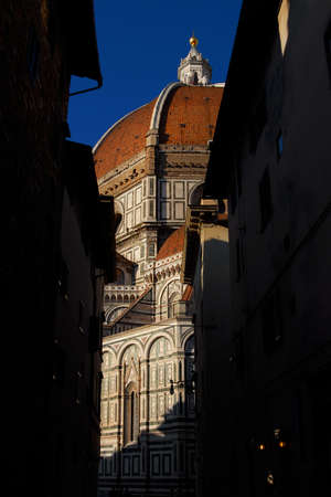Partial view of Santa Maria del Fiore (St Mary of the Flower) in Florence from a narrow lane, built by italian architect Brunelleschi in the 15th century, a symbol of Renaissance in the world