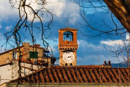 Lucca medieval 'Torre delle Ore' (Clock Tower), a city landmark, seen through tree bare branches Archivio Fotografico