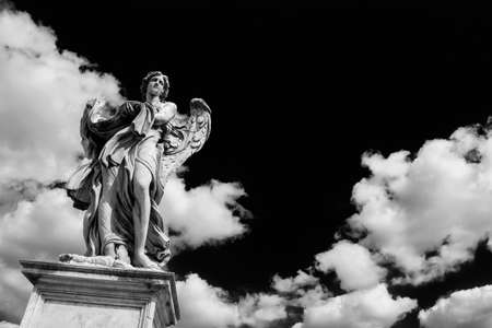 Angel statue holding the garment and dice of Jesus Passion with heavenly clouds. A 17th century baroque masterpiece at the top of Sant'Angelo Bridge in the center of Rome (Black and White with copy space)