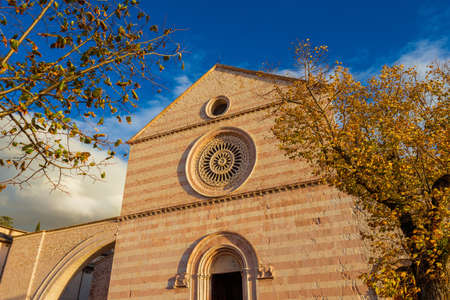 Autumn in Assisi. St Claire medieval gothic church with autumnal leaves
