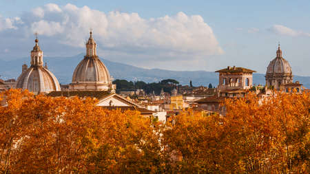 Rome autumn skyline. Baroque domes rise above beautiful red and orange leaves