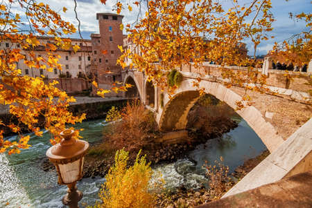 Autumn and foliage in Rome. Orange and yellow leaves near Tiber Island with ancient roman bridge, in the city historic center