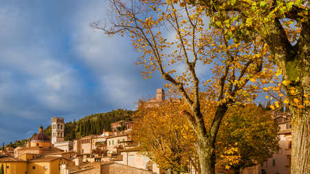 Autumn in Assisi. View of the city ancient buildings with autumnal leaves and beautiful clouds Stock Photo