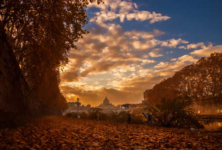 Autumn and foliage in Rome. Beautiful red leaves, golden sunset light and evening haze create a magic autumnal atmosphere along River Tiber in the city historic center