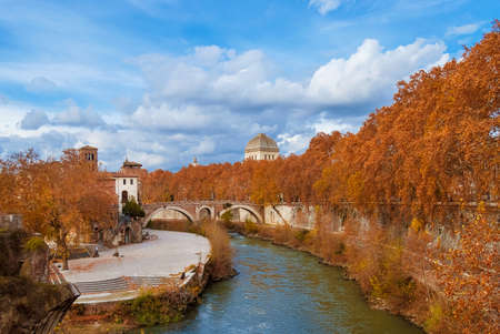 Autumn and foliage along River Tiber. Beautiful red, orange and yellow leaves near Tiber Island in Rome historic center