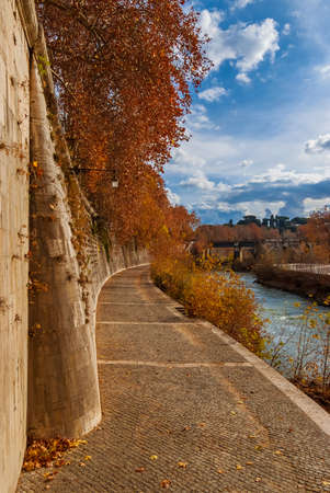 Autumn and foliage in Rome. Beautiful red, orange and yellow leaves along River Tiber banks