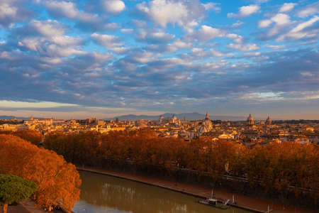 Rome historic center skyline at sunset with Tiber River and autumn red leaves Stock Photo