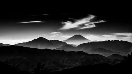 Iconic Mount Fuji wrapped in misty clouds like and old painting, seen from Mount Takao in Japan (Black and White)