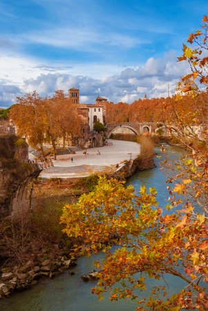 Autumn and foliage along River Tiber. Beautiful red, orange and yellow leaves near Tiber Island in Rome historic center, seen from Palatine Bridge