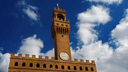 Palazzo Vecchio (Old Palace) clocktower among clouds, the beautiful Florence town hall erected in the 14th century and designed by the famous medieval architect Arnolfo di Cambio