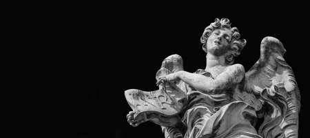 Angel in ecstasy statue holding Jesus Inri sign on black