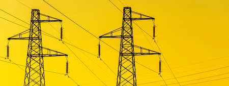 Energy Transmission towers or electricity pylons with wires, cables against golden sky