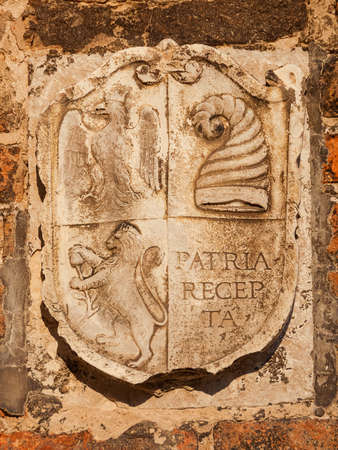 Old heraldic emblem with imperial eagle, doge's hat (horn) and lion on a Venice bricl wall