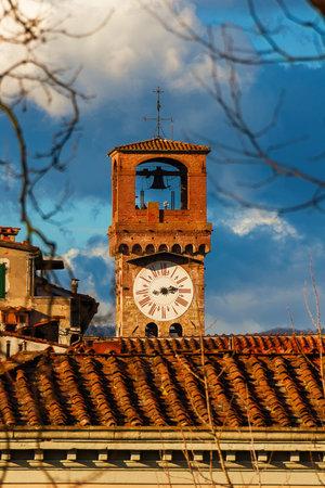 Lucca medieval 'Torre delle Ore' (Clock Tower), a city landmark, seen through tree bare branches Foto de archivo