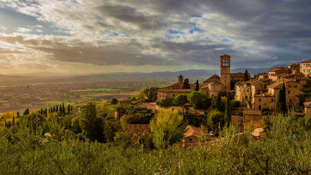 View of the Assisi historic center ancient buildings and nearby countryside at sunset with beautiful clouds