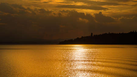 Golden sunset light over Lake Trasimeno and Isola Maggiore (Greater Island) in Umbria