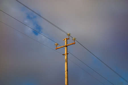 Very old electricity pylon with wires, cables against cloudy sky Foto de archivo