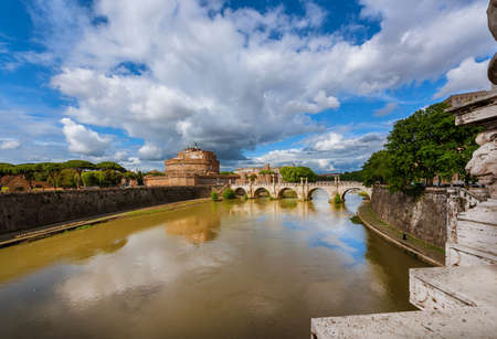 View of River Tiber with the Holy Angel Castle and Bridge under a cloudy sky in Rome, from the nearby Victor Emmanuel II Bridge