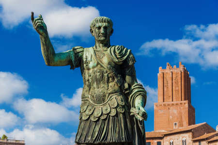 Trajan emperor of Ancient Rome old statue with medieval Tower of Militia in the background along Imperial Fora Road in the historic center of Rome