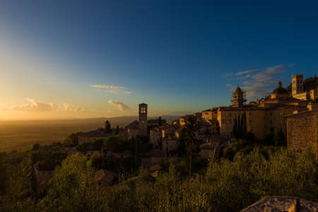 Assisi historic center ancient buildings and Umbria countryside at sunset