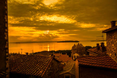 Golden sunset light over Lake Trasimeno, Isola Maggiore (Greater Island) and Isola Minore (Little Island) in Umbria, from Passignano panoramic terrace