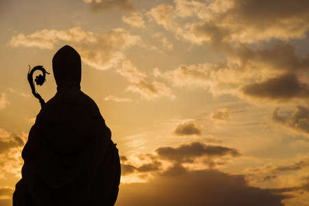 Christian Religion and Spirituality. Bishop ancient statue silhouette with crosier against a sunset sky Foto de archivo