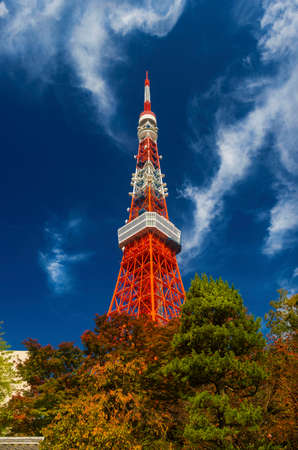 Autumn in Japan. Tokyo Tower rises over autumnal leaves among swirling clouds