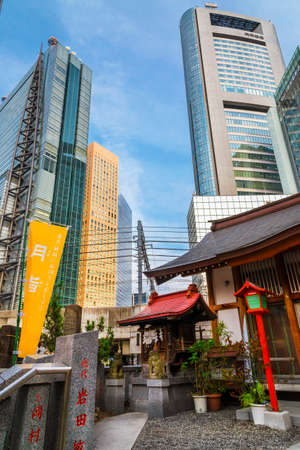 Tradition and Modernity in Japan. View of Shimbashi-Shiodome modern skyscrapers behind the red gate of Hibiya Shrine in downtown