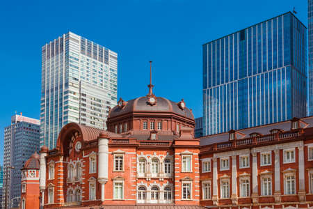 Japan between tradition and modernity. City center modern buildings behinds the old and elegant railways station red brick facade and dome Editorial