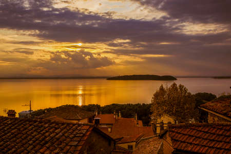 Beautiful sunset over Lake Trasimeno Isola Maggiore (Greater Island) and Isola Minore (Little Island) in Umbria, from Passignano old town Foto de archivo