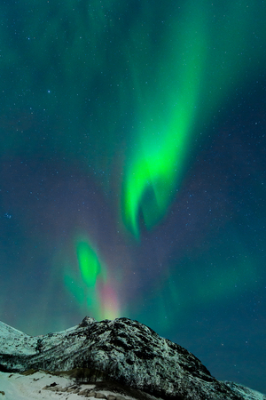 The birth of the aurora borealis on a perfect night by the mountains Stock Photo