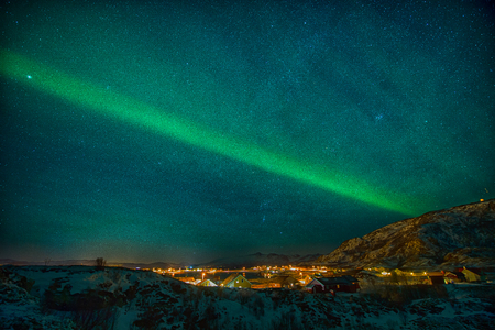 The Northern Lights trace a definite line in the sky to illuminate a city in Norway Stock Photo