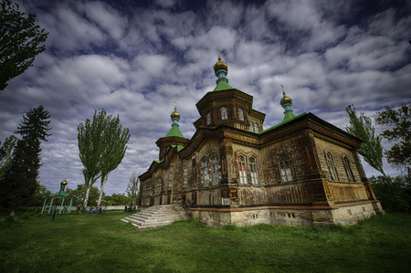 beautiful wooden church in Kyrgyzstan with a sky full of clouds