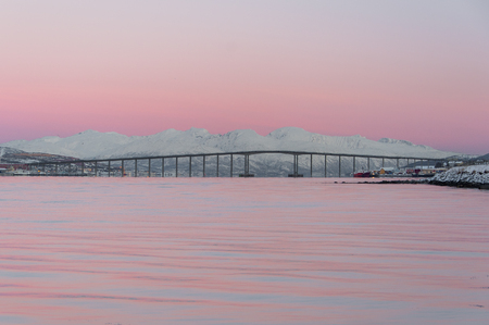 tromso bridge with pink sky and white mountains
