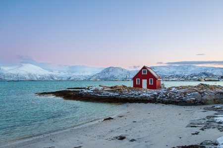 red house on the frozen bay of norway