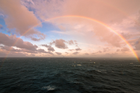 rainbow in the middle of the sea with a beautiful blue sky full of clouds