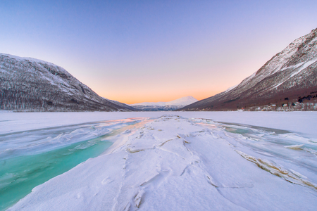 beautiful frozen fjord with fog and turquoise water