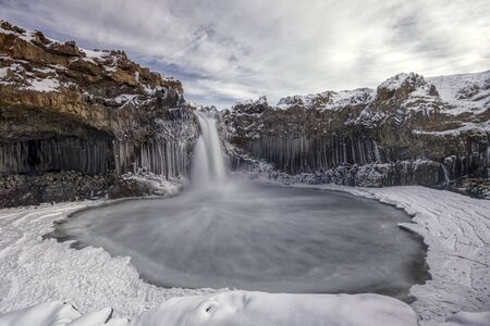 waterfall of Aldeyjarfossin iceland surrounded by ice