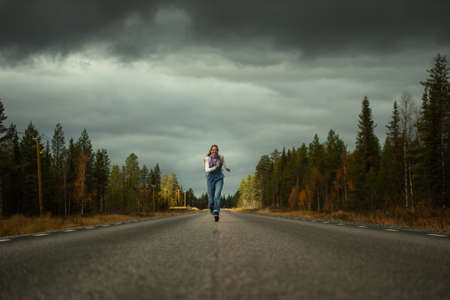 woman runs on a road in the autumn forest