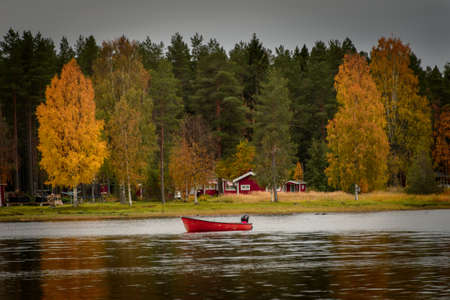 little red boat on the lake in autumn near the typically Norwegian red houses 版權商用圖片