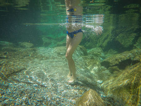 girl swims in the crystal clear green water of a river 版權商用圖片