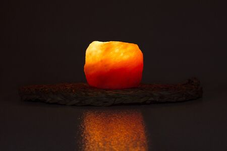 Himalayan Salt Candle Holder with flame on a dark background