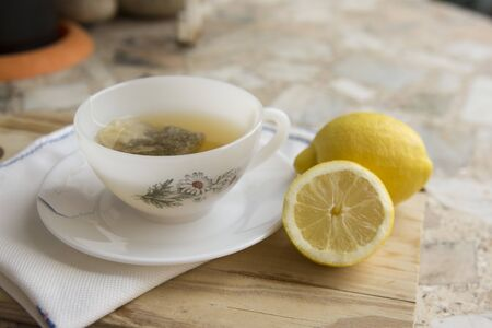 cup of chamomile tea with lemon on a neutral background. Healthy remedy Stock Photo
